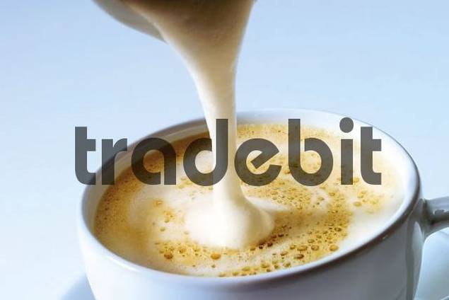 Pouring frothy milk into a cup of cappuccino